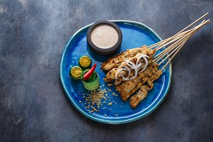 Satay ayam or malaysian meat skewers with peanut saucem copyspace