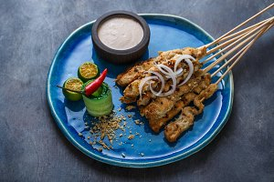 Close view of sate ayam or chicken skewers with peanut sauce