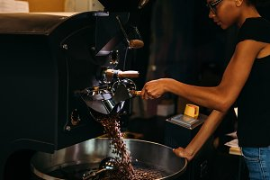 Young barista working with roaster