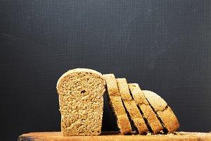 Sliced bread on wooden board. Dark
