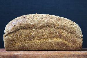 Bread on wooden cutting board. Side