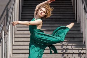 Beautiful girl dancing in the city against the backdrop of a stone staircase.