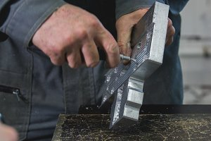 Male working hands grinds the metal detail with a scraper