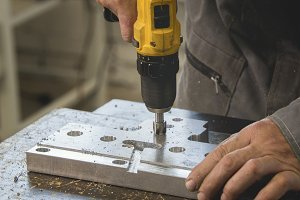 Male working hands drilling industrial metal object