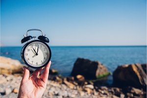 Hand hold watch on beach background.Alarm clock on sea and sand background different time with summer vacation.Vacation time concept.
