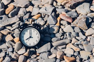 Vacation time. Alarm clock on the beach