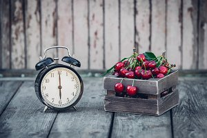 Summer Time, red cherry and an Alarm Clock on an Old Wooden Table