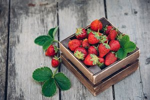 Fresh juicy strawberries with leaves. Rustic wooden box and handmade lace. Retro magazine picture. Strawberry with copy space