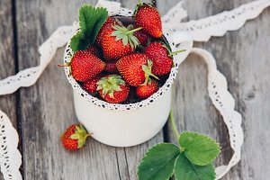 Fresh juicy strawberries with leaves. Rustic enameled mug and handmade lace. Retro magazine picture.