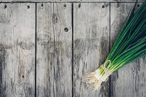 Fresh green onion on a wooden background. Top view. Free space for your text.