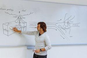 Teacher writing on blackboard