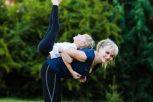 Mother and daughter doing yoga exercise outdoors. Happy family