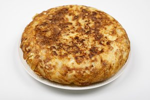 Omelette with potatoes on white background, isolated. Typical spanish food.