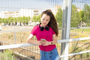 Pretty teenager girl with headphones and mobile in hands. Fashion Technology