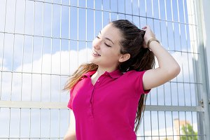 Pretty teen girl with pink short-sleeved sweater touches her hair. Fashion