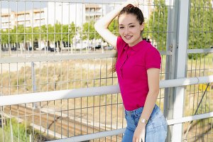 Pretty teen girl with pink short sleeve pullover poses for the camera. Fashion