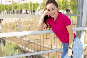 Pretty teen girl in pink short-sleeved sweater is leaning on a railing. Fashion