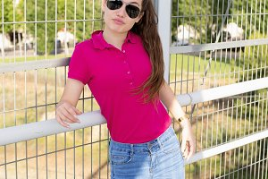 Beautiful and rebellious teenage girl with sunglasses and pink pullover on the street. Fashion