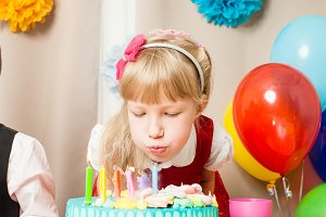 cute girl is blowing the candles