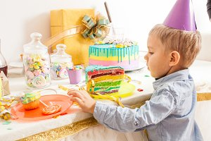 cute boy with party hat wants sweet cake