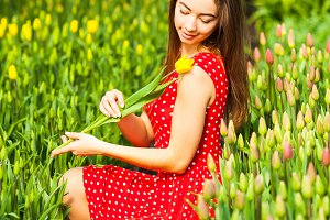 Beautiful woman sitting in a red tulips field at sunset.