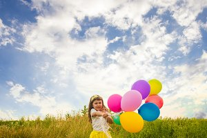 child with colorful toy balloons