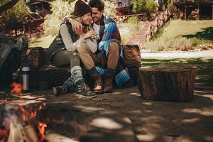 Romantic couple sitting near bonfire