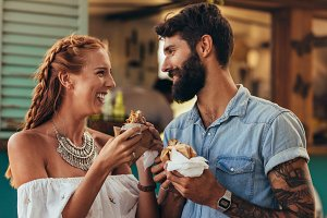 Couple enjoying eating food truck