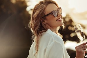 Smiling woman in sunglasses drinking