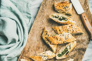 Freshly baked Turkish borek roll cut in slices, square crop