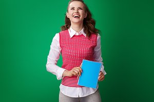 smiling student woman with blue notebook looking at copy space