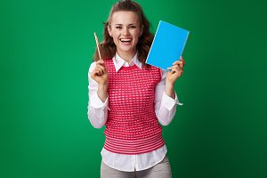 student woman showing blue notebook and pen on green background