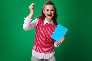 happy young student woman with blue notebook fingers snapping
