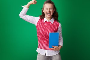 smiling young student woman with blue notebook showing biceps