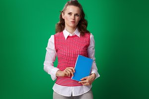 pensive student woman with blue notebook on green background