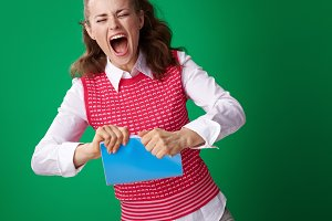 angry student woman tearing blue notebook on green background