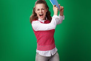 student woman throwing blue notebook against green background
