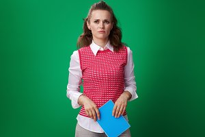 unhappy student woman with blue notebook isolated on green