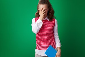 student woman with blue notebook facepalm isolated on green