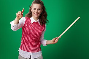 student woman with pointer pointing in camera isolated on green