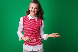 happy young student woman with pointer against green background