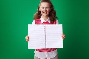 smiling young student woman showing notebook blank page