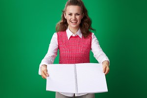 smiling student woman giving open notebook isolated on green