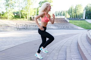 Photo of curly-haired athletic woman running through park among benches