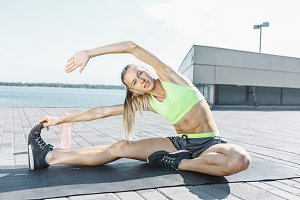 Fit fitness woman doing stretching exercises outdoors at park