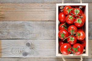 Tomatoes in box on wooden table
