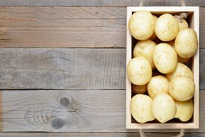 Raw potatoes in box on wooden table