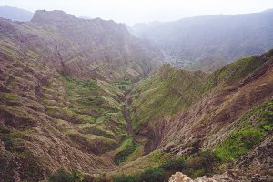 Breathtaking panorama of a steep gorge with haze riverbed and lush green vegetation in the valley of Delgadinho mountain ridge. Santo Antao, Cape Verde