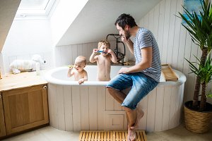 Father with two toddlers brushing teeth in the bathroom at home.