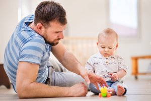 Young father playing with a baby son at home.